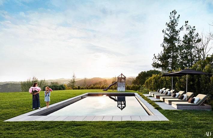 шикарная зелёная площадка во дворе с бассейном и шезлонгами