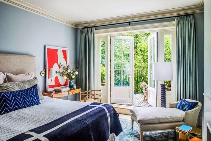 уютная спальня в зелено-голубых цветах с балконом и собакой