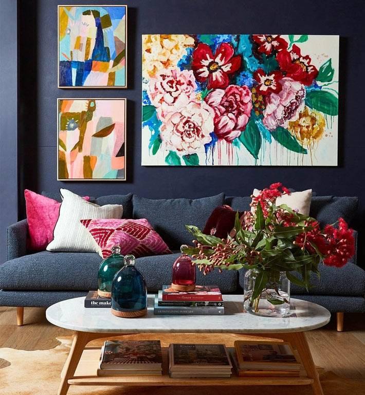 темно серый диван, темные стены гостиной и яркие картины фото