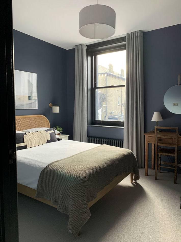 темно-синие стены в спальне, деревянная кровать из ротанга
