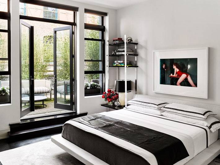 незагроможденный интерьер спальни с выходом на террасу