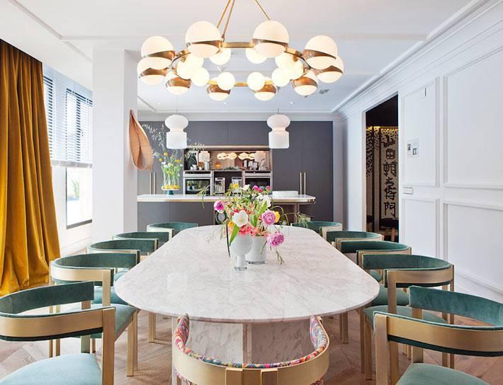 мраморный обеденный стол и зеленые бархатные стулья фото