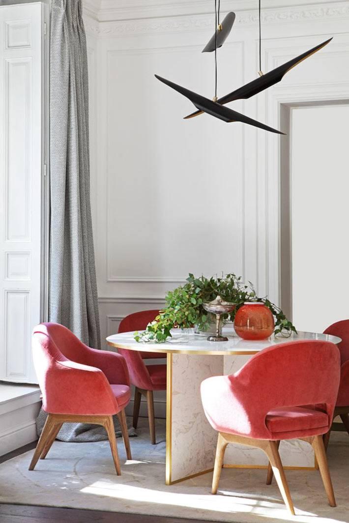 стильная необычная люстра, круглый стол из мрамора и красные кресла