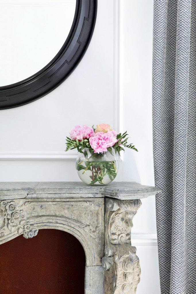 стеклянная ваза с цветами на каменном портале камина