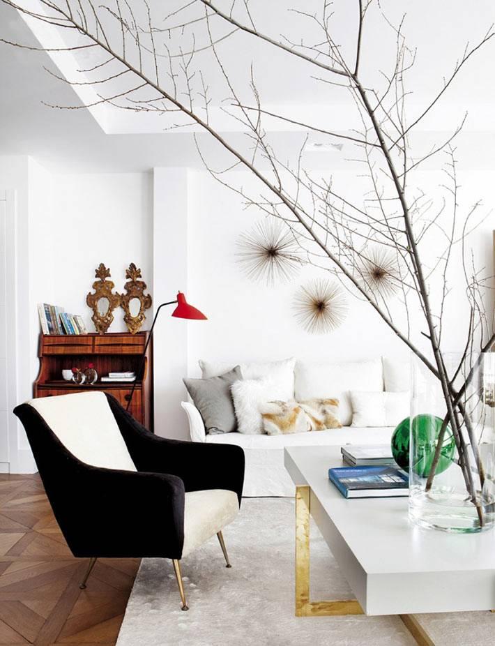 черно-белое кресло, ветки дерева в декоре комнаты, красный торшер