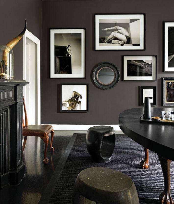 черно-белые фотографии на черной стене в интерьере