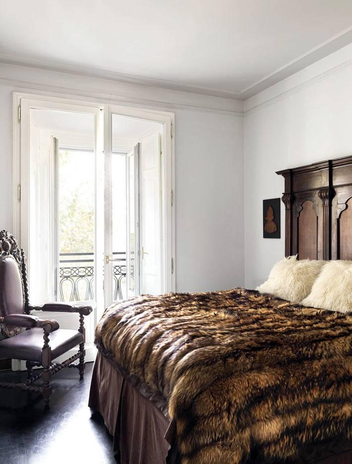 одеяла из шкур на кровати в спальне, старинный стул-трон