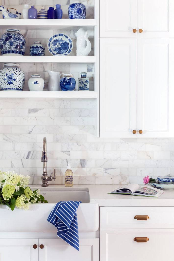 фарфоровые вазы и тарелки с синей росписью на полках кухни