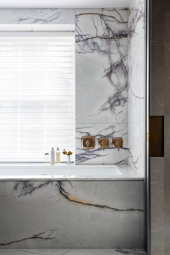 сочетание мраморных плит на стенах и золотых деталей в ванной