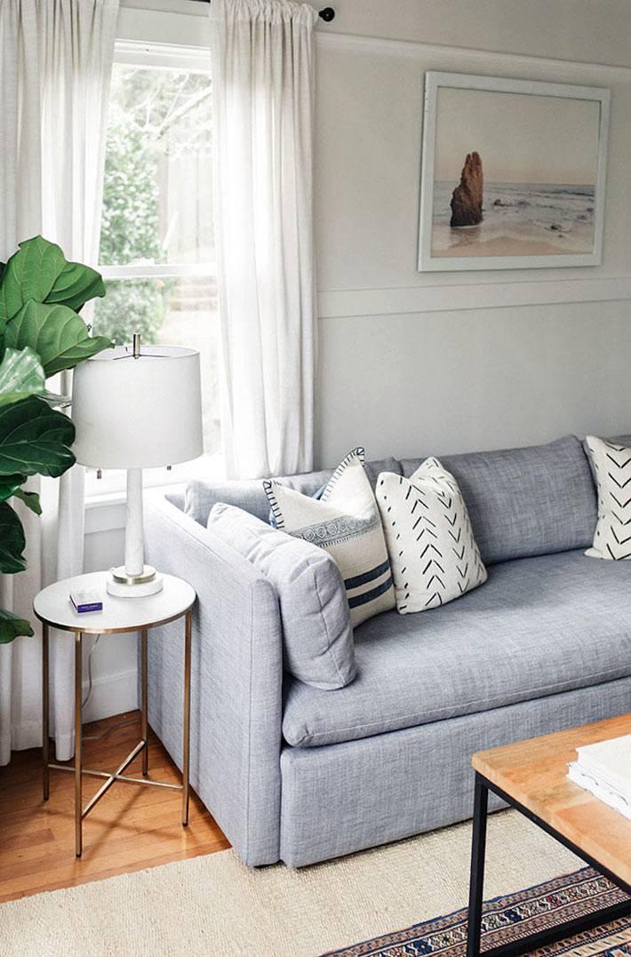 серый диван, белые подушки, маленький прикроватный столик
