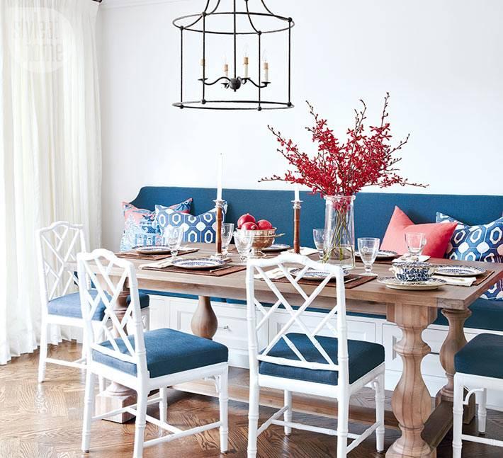 синий кухонный диван, светлые стулья, масивный деревяный стол