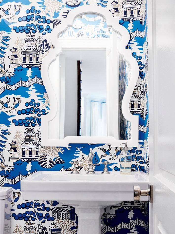 синие расписные обои, зеркало в фигурной белой раме