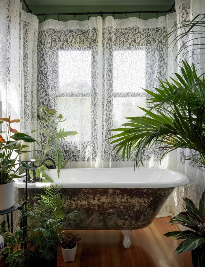 крудевные шторы на окнах и живые цветы в интерьере ванной