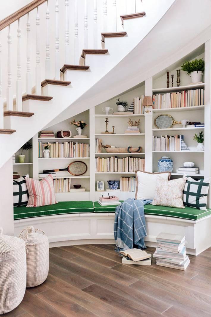 зеленая мягкая скамья возле книжных полок под ступеньками