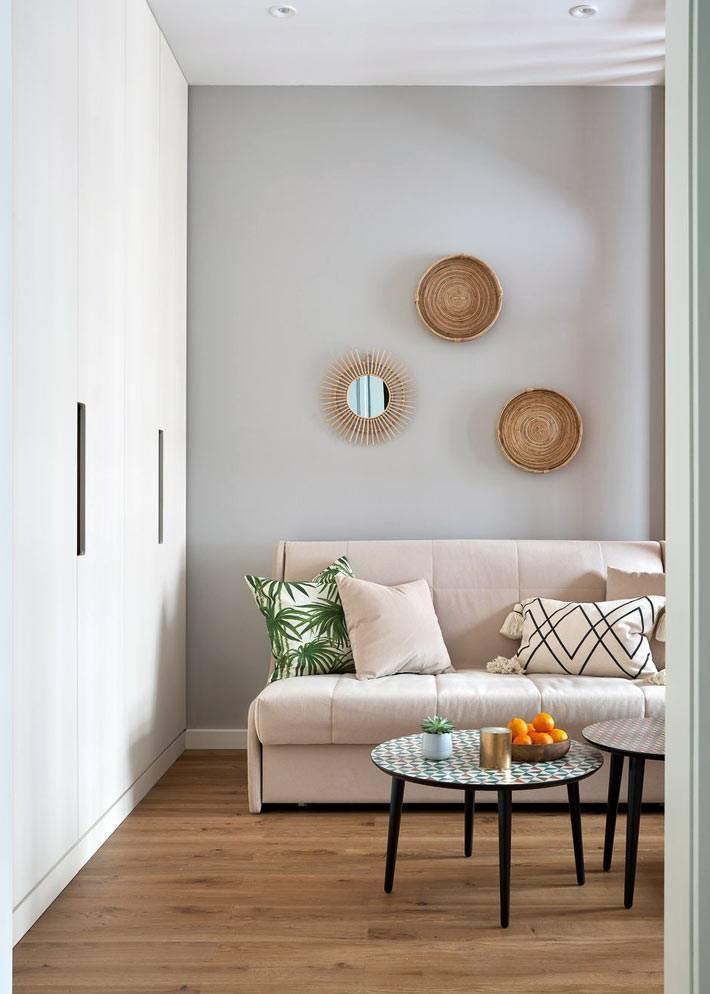 плетеные тарелки на стене над диваном в гостиной фото