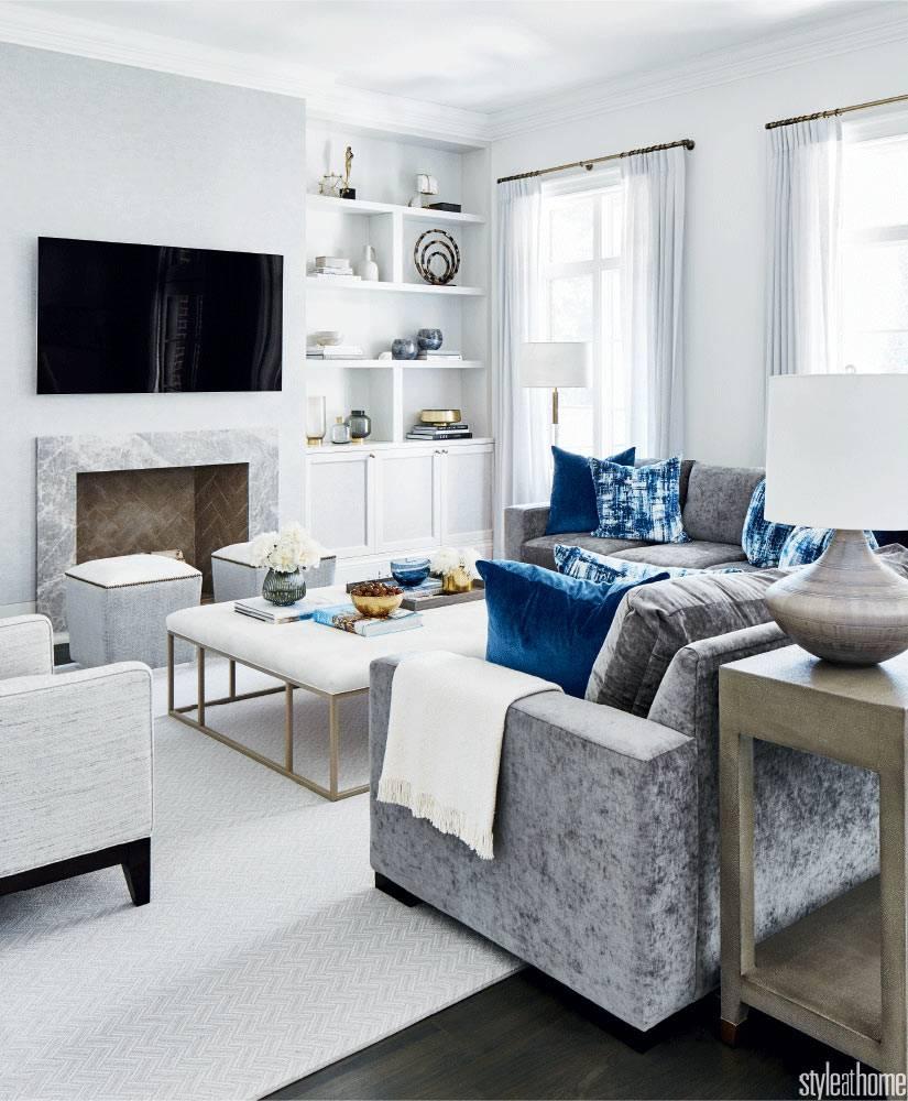 гостиная оформленная в белом цвете с серым бархатным диваном