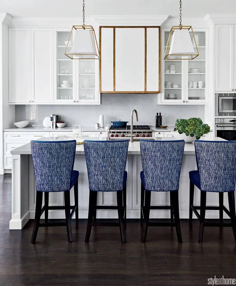 белый интерьер кухни с синими стульями за отдельным островом