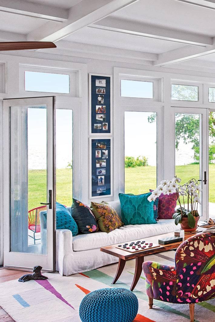 летний дом с разноцветными подушками на диванах