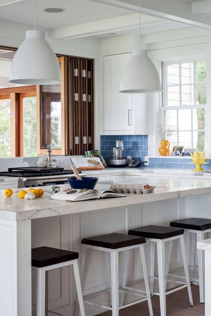 остров на кухне с мраморной столешницей и подвесными лампами