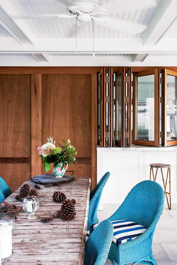 плетеные кресла голубого цвета за деревянным столом