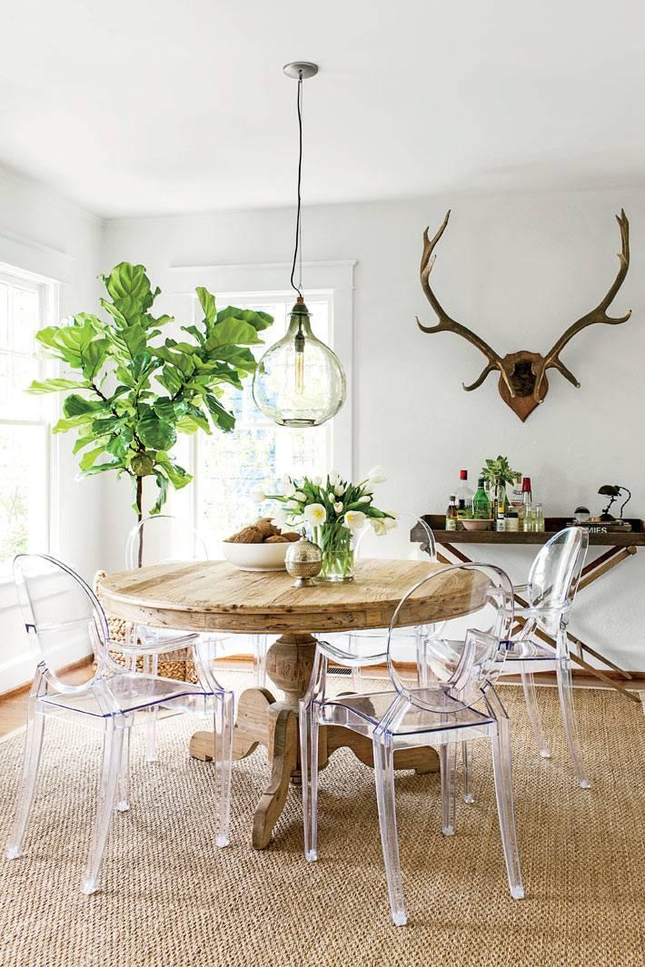 кухонная зона с деревянным столом и прозрачными пластиковыми стульями