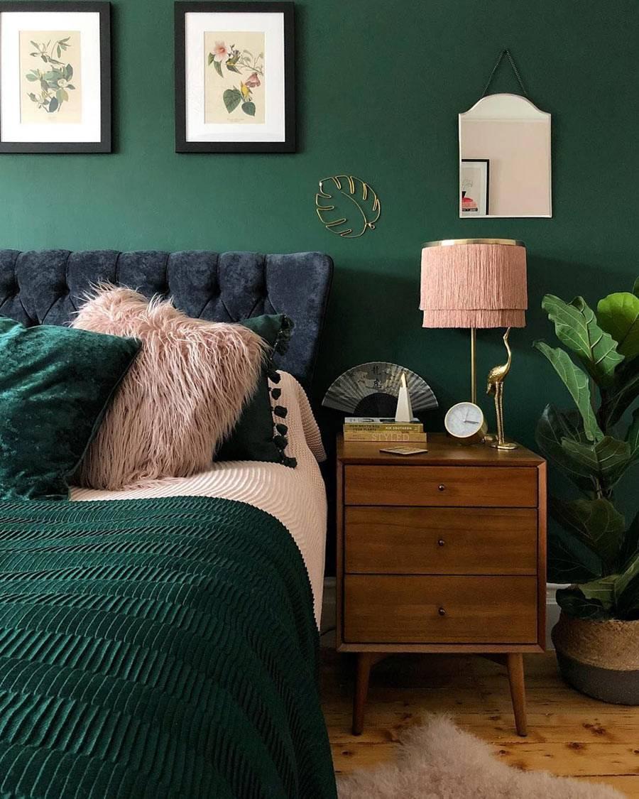 тёмно-зеленые стены в спальне, кровать с бархатным изголовьем, розовый абажур лампы