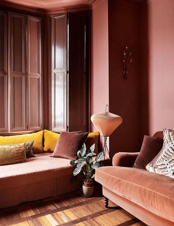 комната со ставнями с розовыми стенами и розовым диваном