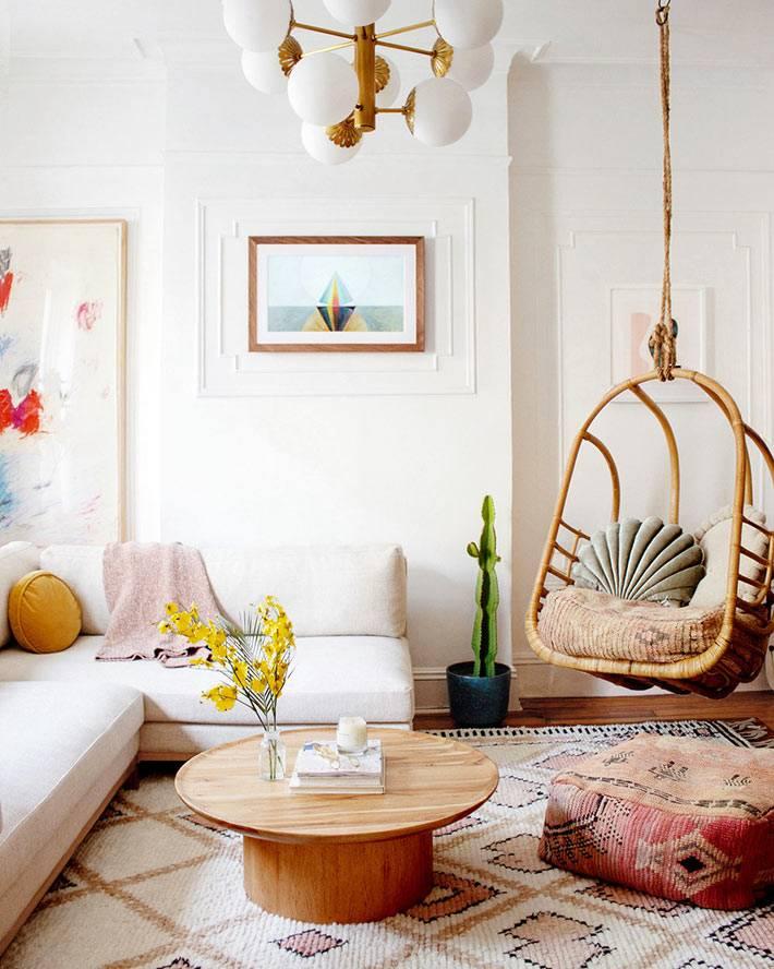 подвесное кресло-качеля из лозы в центре гостиной комнаты