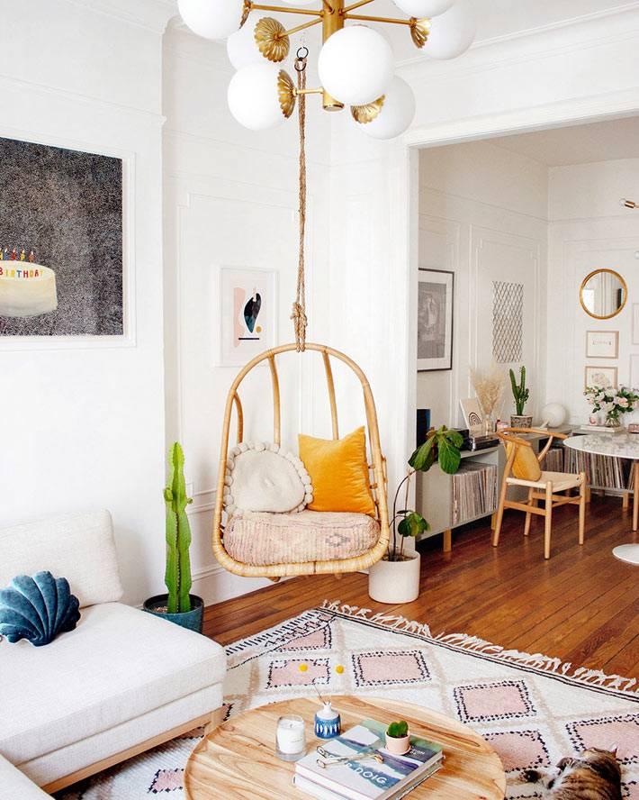 гостиная комната объединена со столовой зоной, красивый ковер на паркетном полу