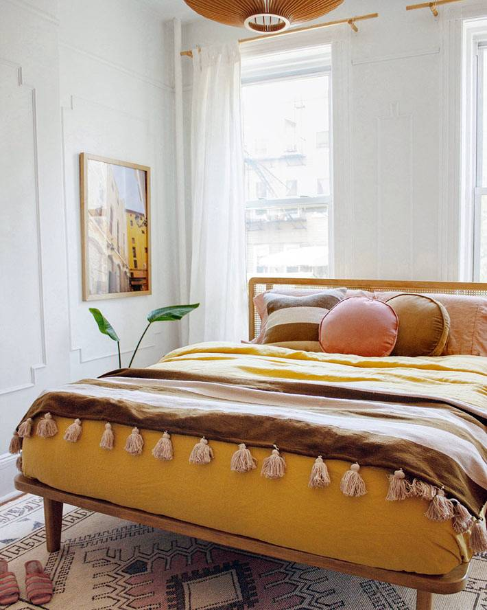 красивый текстиль оранжевого цвета в спальне, диванные подушки на кровати