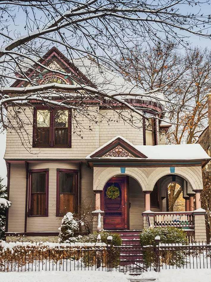 красивый фасад заснеженного дома к новогодним праздникам