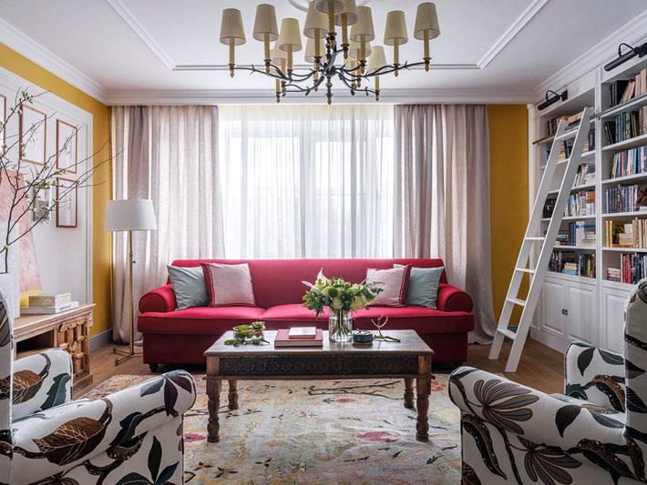 желтые стены в комнате, малиновый диван, пёстрая расцветка кресел