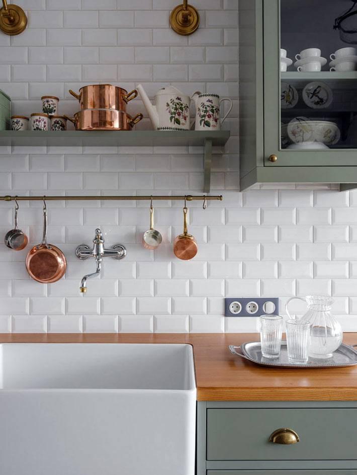 кухонный фартук из белой глянцевой плитки, медная посуда на кухне