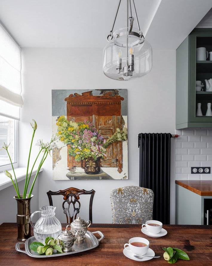 черные радиаторы на белой стене кухни, прозрачная люстра над обеденным столом