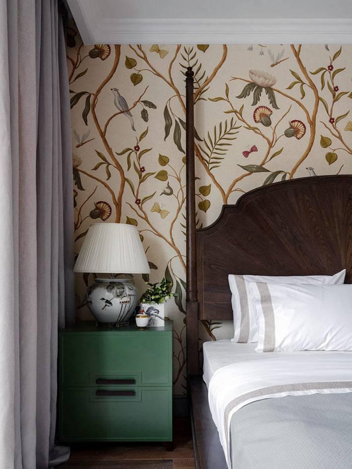 зелёная прикроватная тумба, кровать из тёмного дерева, обои с рисунком птиц