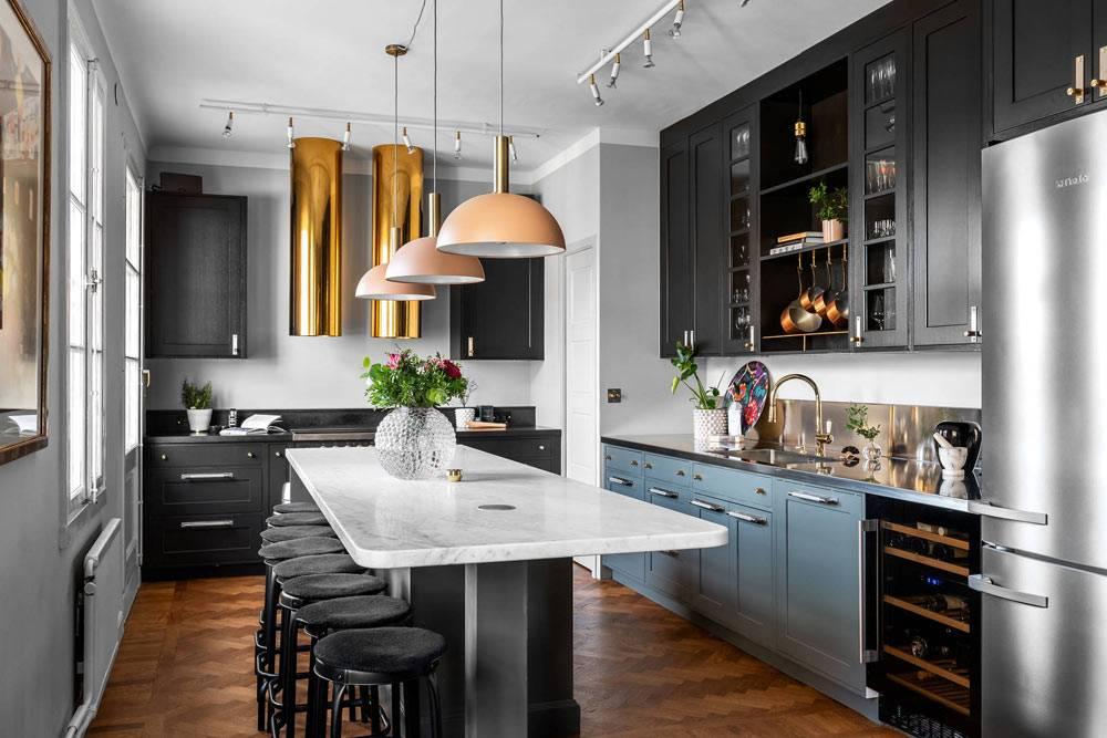 большая кухня в скандинавской квартире с черной кухонной мебелью