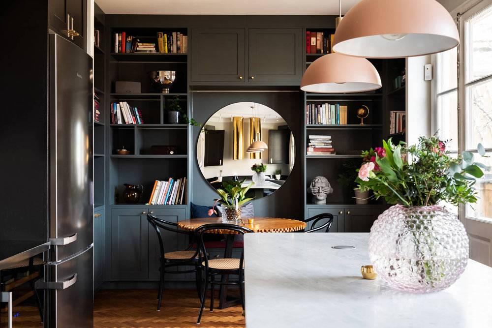 стол-остров белого цвета среди черной кухонной мебели фото
