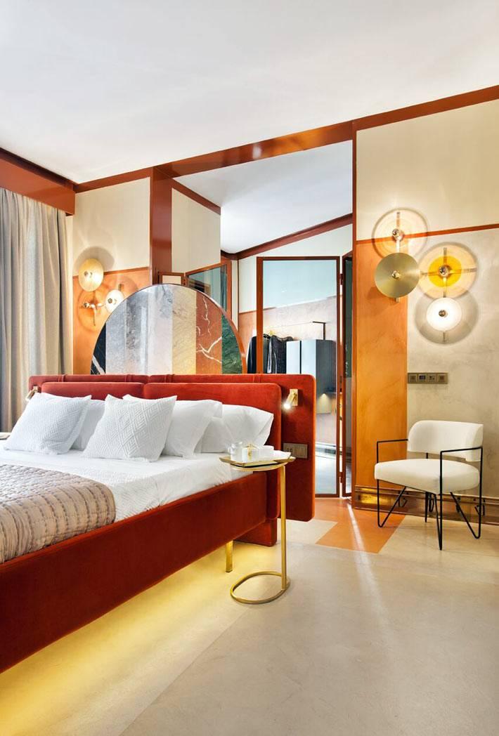 кровать обитая красным бархатом, прикроватный столик с золотистой ножкой
