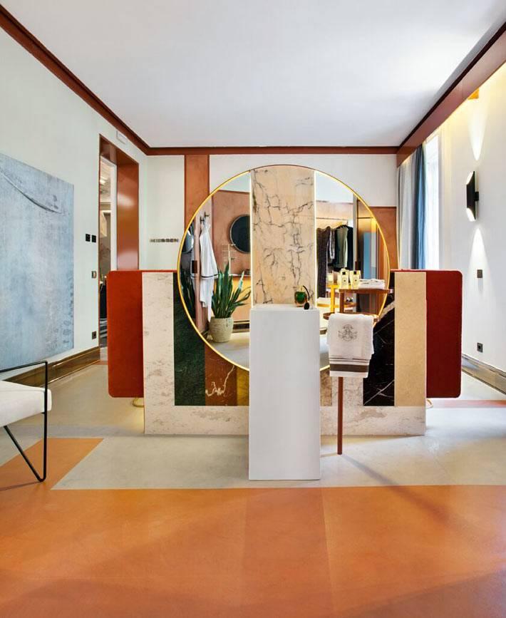 большое круглое зеркало в золотистой раме во всю стену
