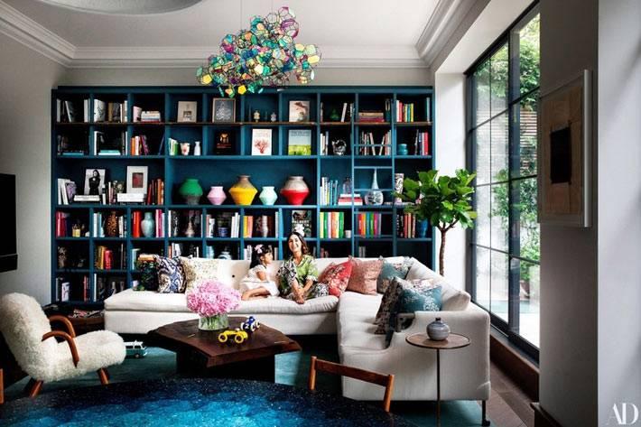 стеллаж для книг синего цвета, разноцветная стеклянная люстра в комнате