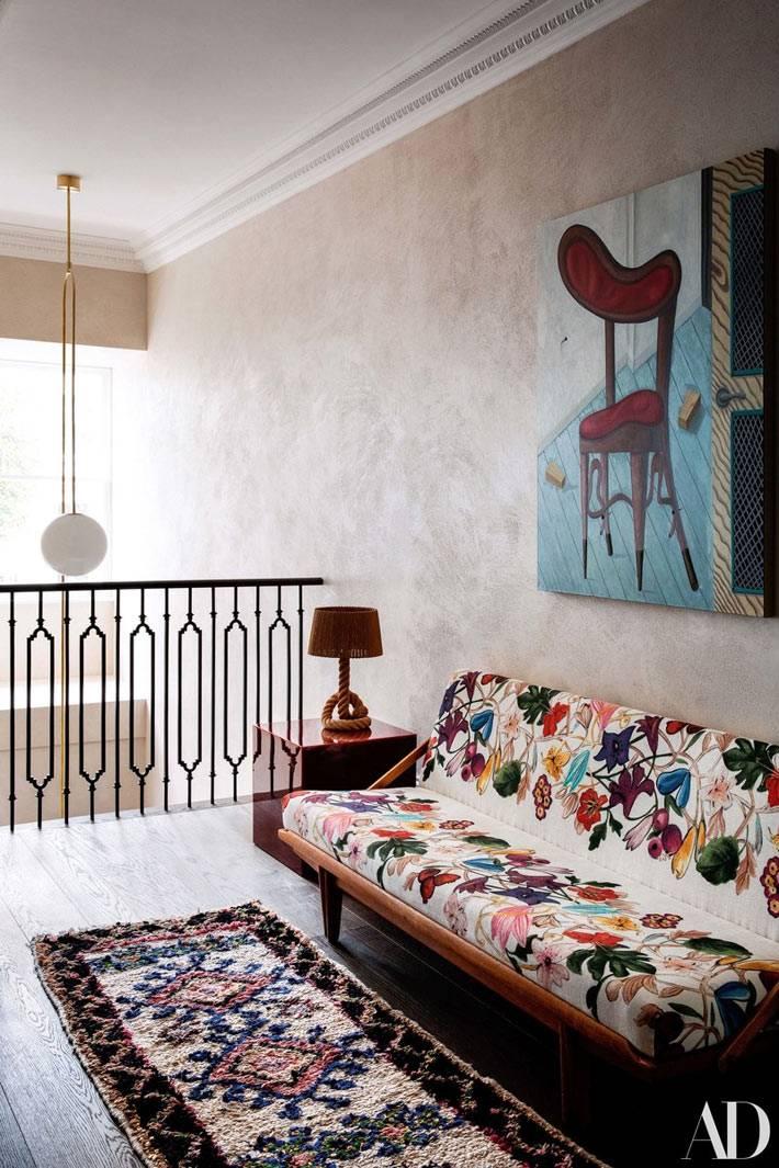 белый диван с пестрой цветочной расцветкой на лестничной клетке