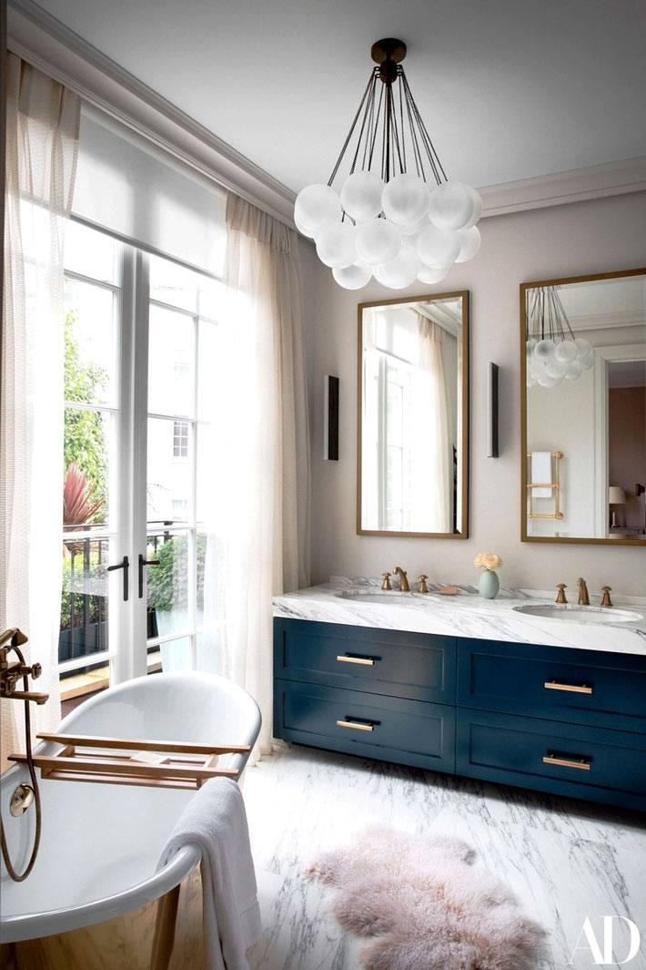 синяя тумба под раковиной с мраморной столешницей в ванной