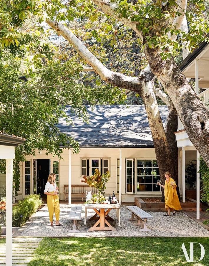 прекрасный уютный двор возле дома с деревьями