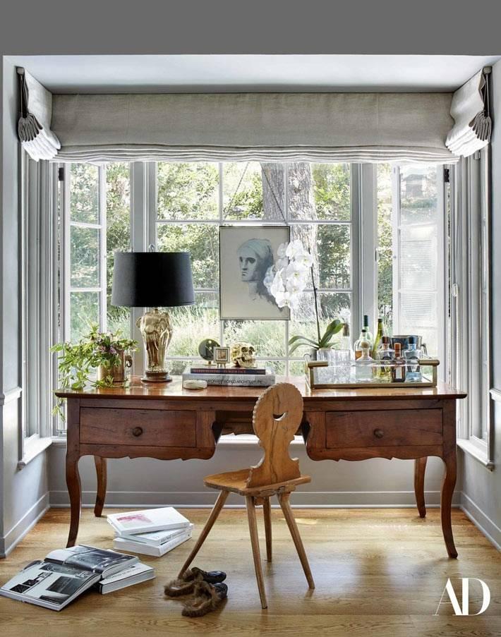 красивый резной рабочий стол возле большого окна с видом на лес