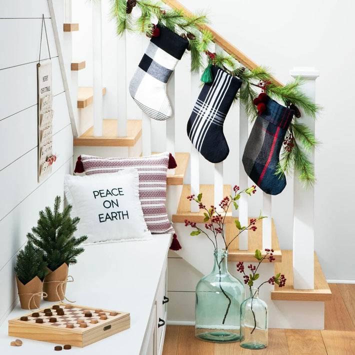 новогодние носки для подарков от санты на перилах лестницы