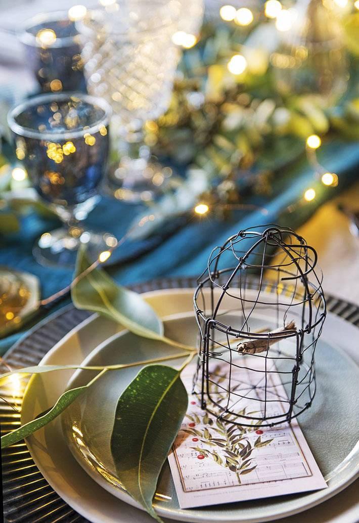 каждая тарелка украшена веточкой омелы и декоративной клеткой для птиц