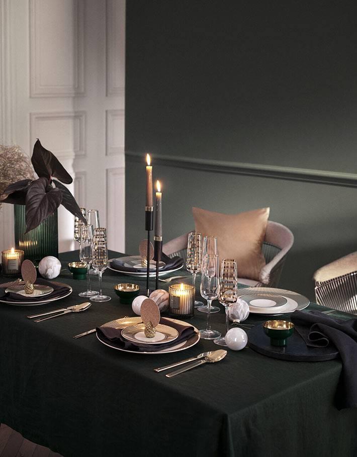 темно-зеленая скатерть и золотые украшения в сервировке стола