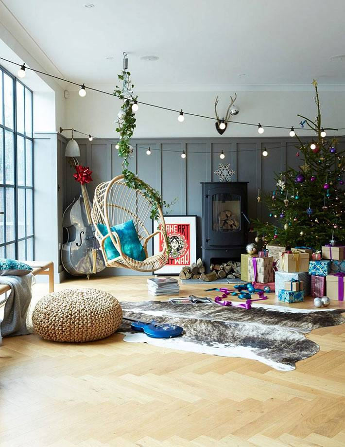 подвесное кресло в комнате, шкура животного на полу, плетеный пуфик