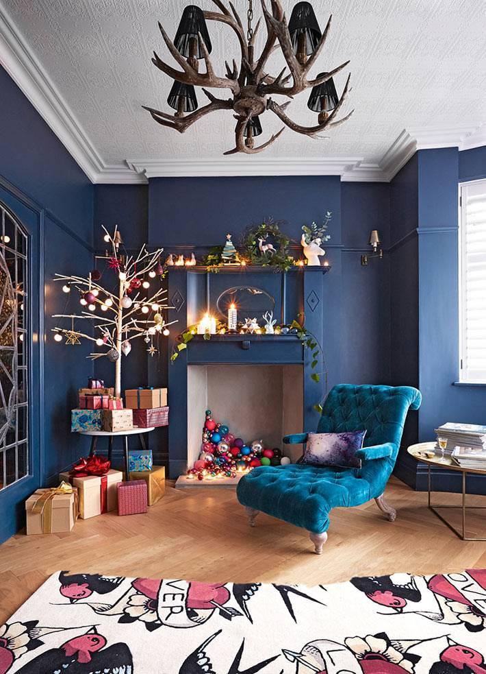 новогоднее украшение комнаты, синие стены, ёлочные шары в декоративном камине