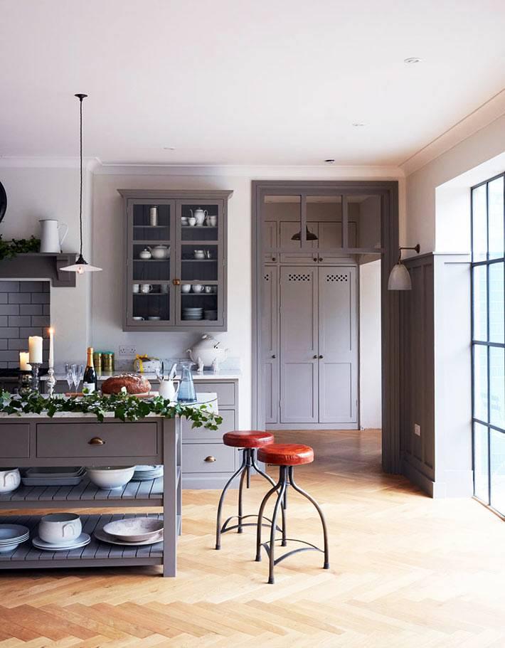 интерьер кухни в пастельных тонах с серой мебелью и красными стульями
